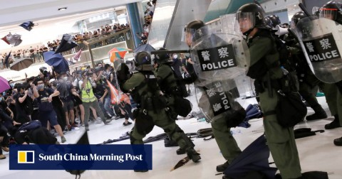 Riot police use pepper spray to disperse pro-democracy activists inside New Town Plaza mall.