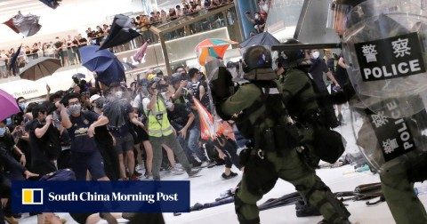 Riot police use pepper spray to disperse protesters in Hong Kong who returned fire with umbrellas and bottles.
